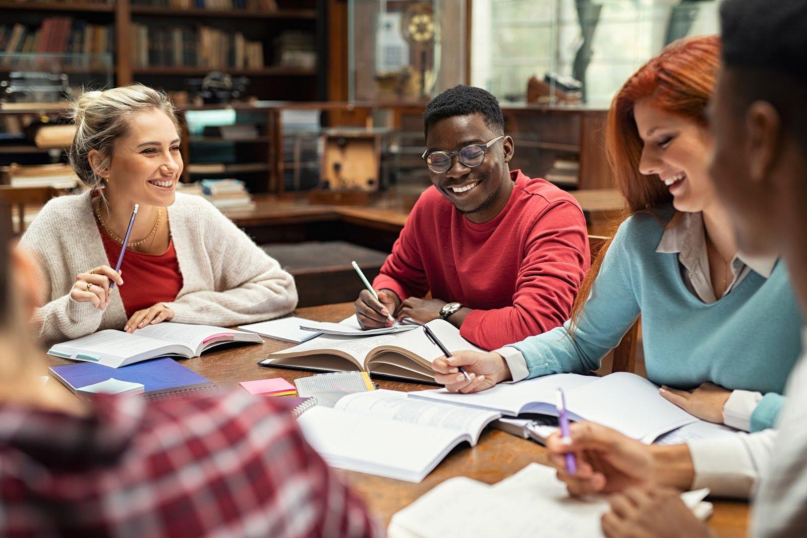 bigstock-Happy-college-students-studyin-365289763
